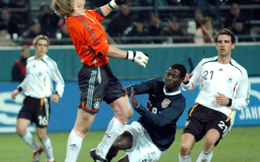 German goalie Oliver Khan and U.S. forward Eddie Johnson converge on a long, bouncing shot toward the end of Germany's 4-1 win over the U.S. on Wednesday in Dortmund. The ball, kicked by U.S. defender Steve Cherundolo, bounced into the goal for the only U.S. score.