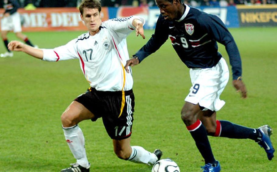 U.S. forward Eddie Johnson dribbles downfield while being defended by Germany's Sebastian Kehl.