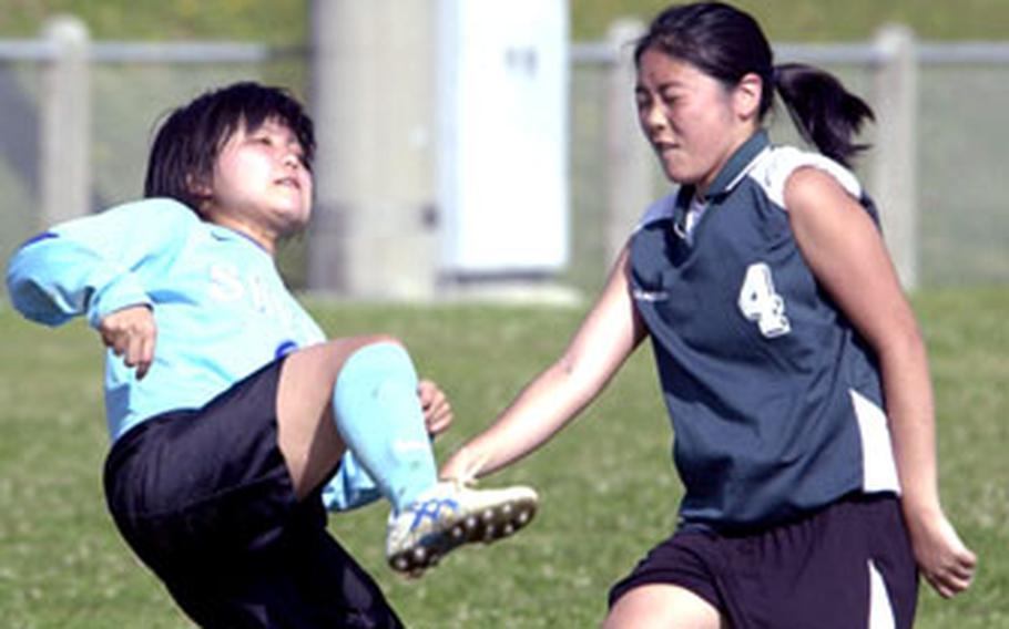 Yurika Ohama, left, of Shuri High School boots the ball over herself and Melissa Minei of Kubasaki during Saturday's girls soccer match at Camp Foster, Okinawa. Kubasaki won 6-0.