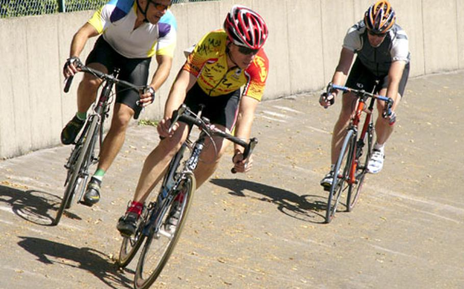 Men's masters champion James Sharp of Hanau, center, and Jeff Clayton of Stuttgart drop down the bank of the Schopp Velodrome in front of Phil Tinsley of Heidelberg during the 13.32-kilometer masters points race in Schopp, Germany, on Saturday.