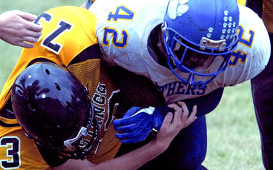 Yokota Panthers running back Anthony McNeill (42) lunges through the tackle of Joey Benus (50) and David Zielinski (73) of the American School In Japan Mustangs during Saturday's game at Mustang Valley, American School In Japan's Chofu campus in Tokyo's western suburbs.