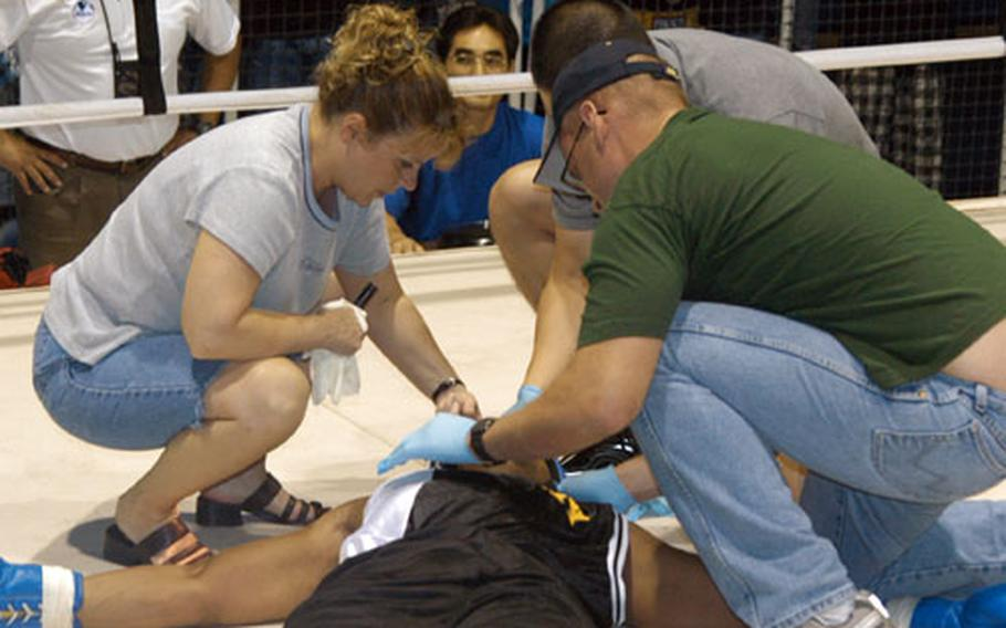 The ringside medical team works to revive Staff Sgt. Geremy Ganaway after he was knocked out in the second round by 2nd Lt. John Rigsbee during the Tough Soldier Boxing Invitational at Camp, South Korea, on Saturday. Medics from Company D, 168th Medical Battalion are Capt. Rachelle Beseman (left), Capt. Jason Park (center) and Sgt. Jeffrey Boyle.
