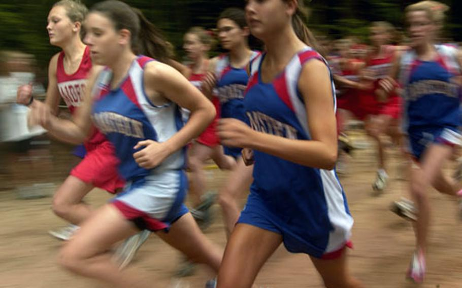 Colleen Smith, left, the returning European champ from Kaiserslautern High School, pushes off the starting line amid a sea of runners during the first cross country race of the season in Vogelweh, Germany, on Saturday.
