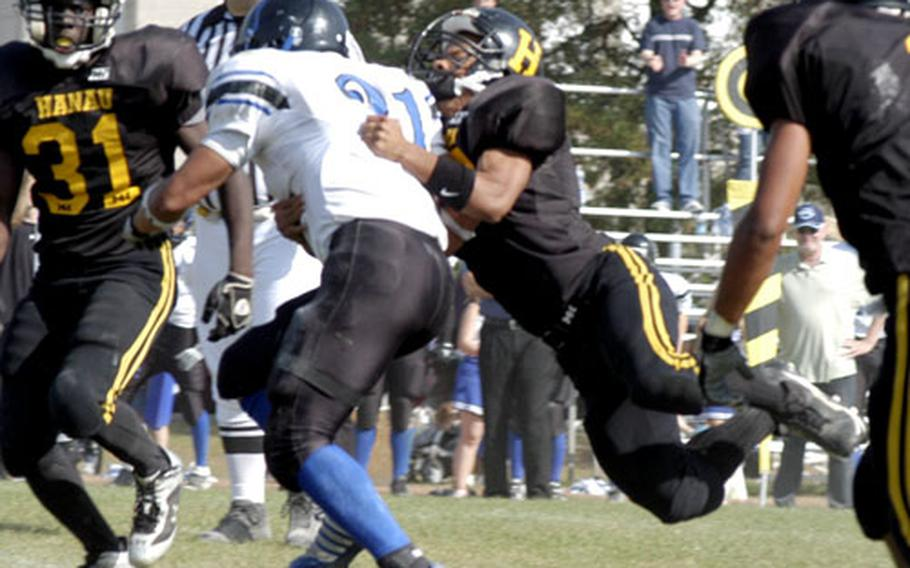 Hohenfels' Sung Byon, 21, takes a Hanau defender for a ride Saturday. Byon had four carries for 30 yards before he had to be taken off the field by paramedics in the second quarter with a suspected knee injury.