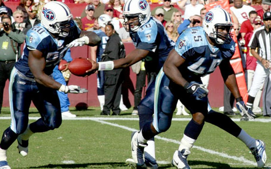 Ahmard Hall, right, blocks as Titans quarterback Vince Young hands off to running back Travis Henry.