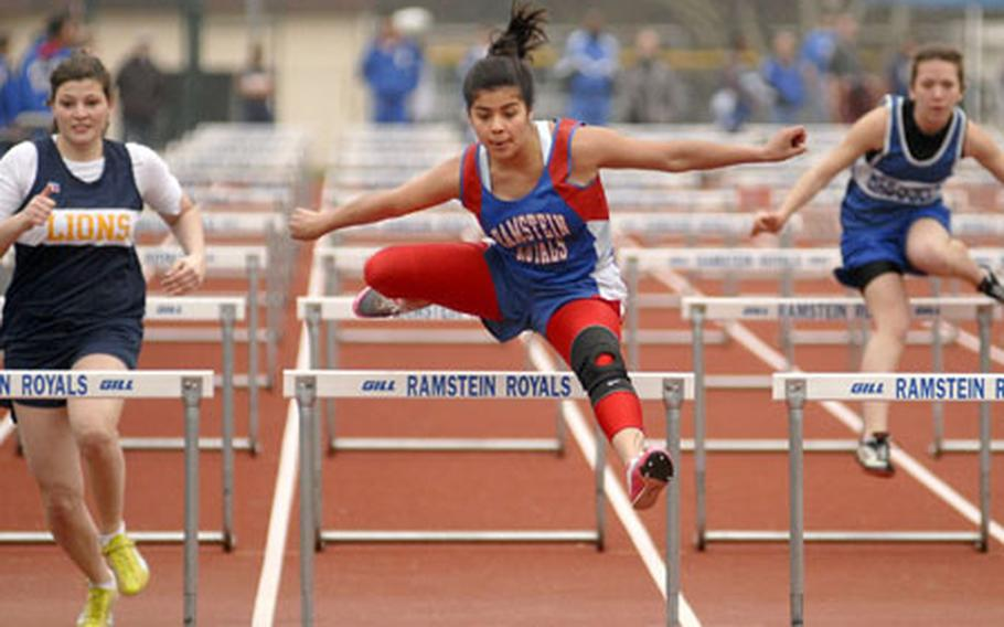 Amanda Garza, a junior from Ramstein High School, soars over the final hurdle during a track meet at Ramstein Saturday. Garza won the 100-meter girls high hurdles with a time of 17.9 Seconds.