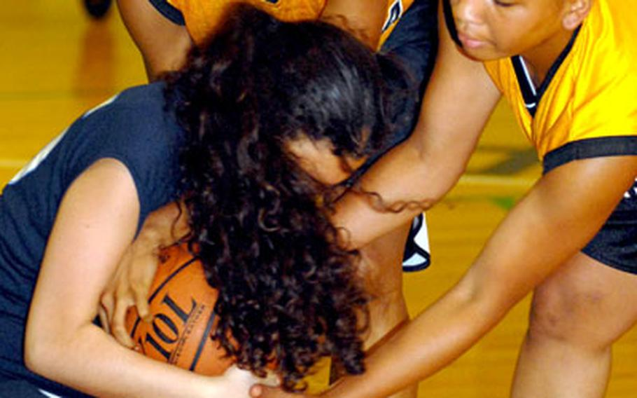 Aja Walker, top, and Monica Hayes, right, of the Kadena Panthers tie up the basketball along with Lena Forte-Ramos of the Bodwell International School Barracudas of North Vancouver, British Columbia, during Wednesday's series of high school basketball games at Camp Foster, Okinawa.