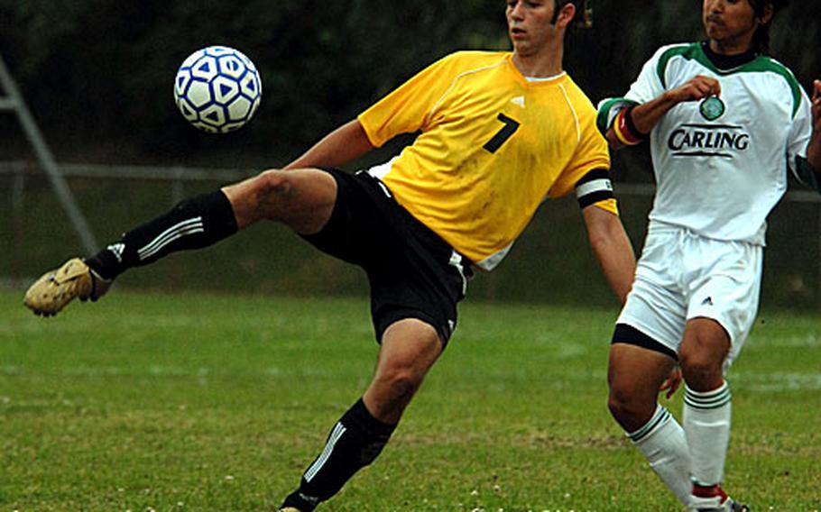 Alex Mierzejewski (7) of the Kadena Panthers boots the ball away from Corey Harter of the Kubasaki Dragons.