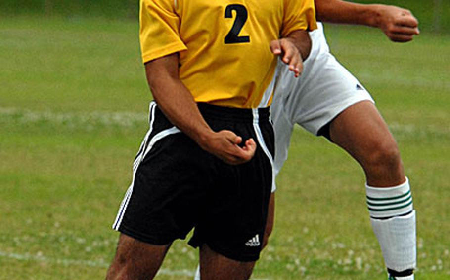 Jacob Bloom (2) of the Kadena Panthers and Isaac Bennett of the Kubasaki Dragons go up to head the ball.