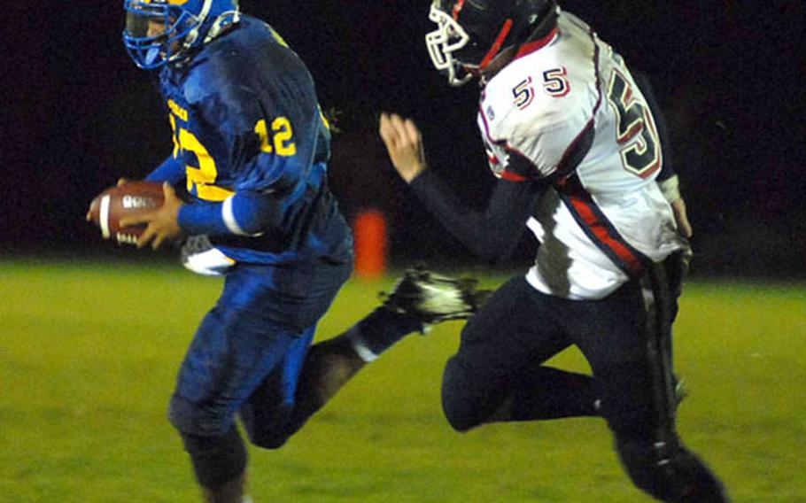 Ansbach quarterback John Willis escapes the grasp of Bitburg's Rob Ferguson in second-half action in the Division II final. After a half tied at 8-8, Willis lead the Cougars to a 44-8 win.