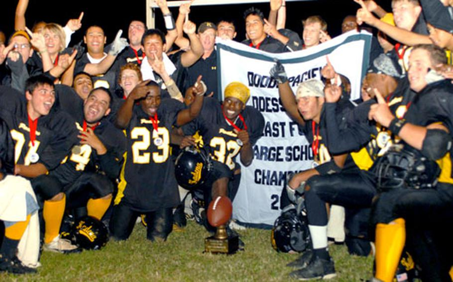 Kadena Panthers football players and coaches celebrate around the banner and trophy after Saturday's Far East High School Class AA football championship game.