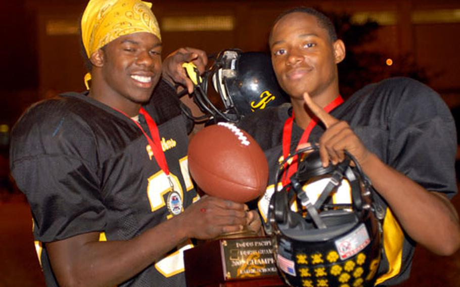 Okinawa rushing champion Ernest Carr, left, and four-touchdown scorer in Saturday's game Brandon Harris of Kadena celebrate with the trophy after Saturday's Far East High School Class AA football championship game.