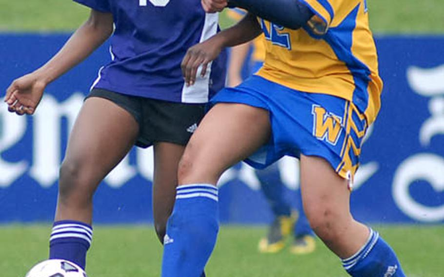 Mannheim's Alanna Crockwell, left, passes off to a teammate in front of Wiesbaden's Danielle Lewis in DODDS-Europe soccer action on Saturday.