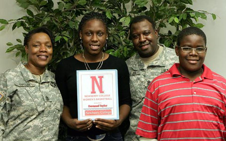 From left, Army Sgt. Maj. Dana Taylor, Seoul American senior forward Devanee' Taylor, Army Sgt. Maj. Darvin Taylor and their son, Darvin, with a national letter-of-intent that Devanee' signed to attend Newberry College in South Carolina.