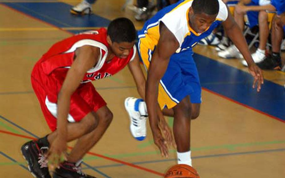 Kenneth Dixon, left, of the E.J. King Cobras and Keron Brown of the Yokota Panthers chase a loose ball.
