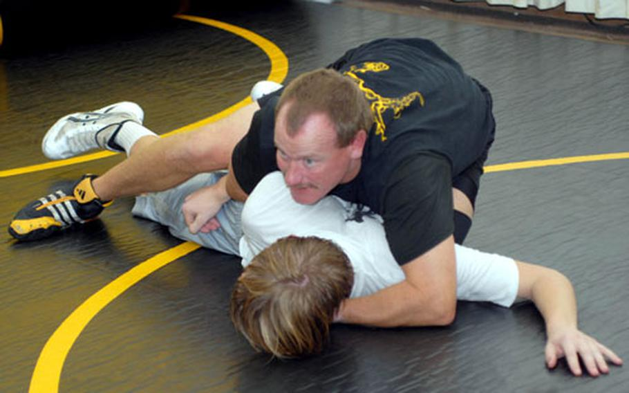 Coach Steve Schrock of the defending Far East High School Wrestling Tournament team champion Kadena Panthers demonstrates technique on sophomore 129-pounder Jacob Bishop during Monday's practice at Panther Pit wrestling annex at Kadena High School. Bishop is a transfer from Zama American and last year's 129-pound runner-up.