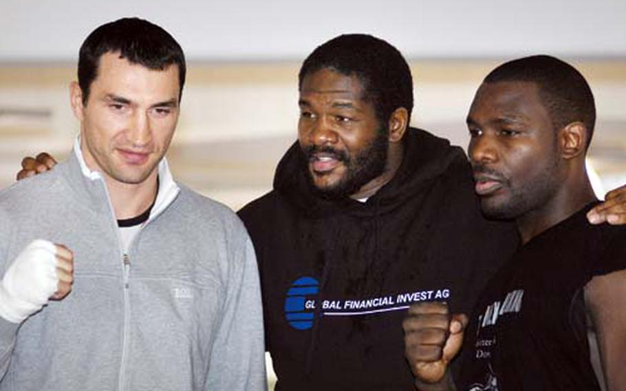 """Riddick """"Big Daddy"""" Bowe, center, poses with IBF/IBO/WBO heavyweight champion Wladimir Klitschko, left, and Klitschko's challenger Hasim Rahman, right, during a press event at a Mercedes-Benz dealership near Heidelberg on Wednesday. Bowe, a former undisputed heavyweight champion, will be fighting on the undercard of the Klitschko-Rahman world title bout scheduled for Saturday night in Mannheim."""