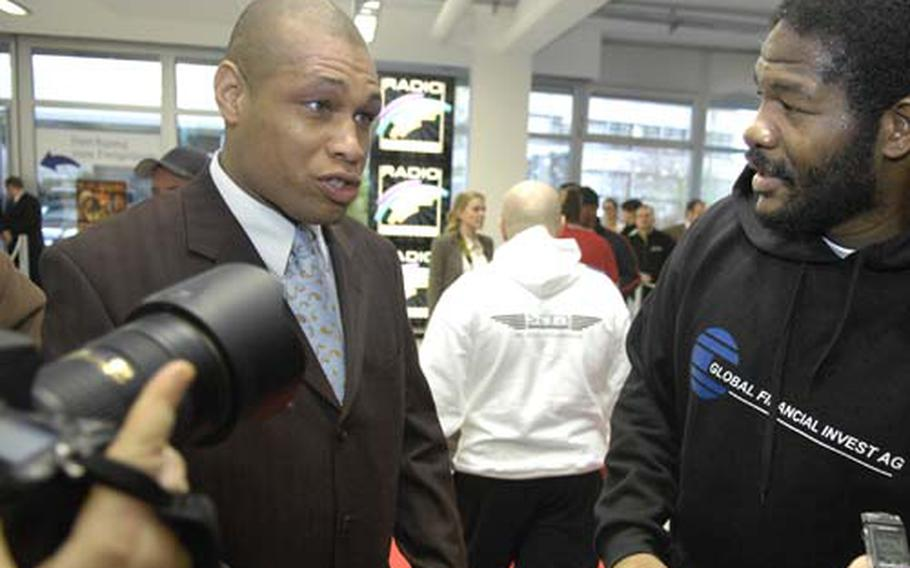 Herb Smith, flanked by Riddick Bowe, talks to the media during a press event at a Mercedes-Benz dealership near Heidelberg on Wednesday. Smith, a civilian for the Army in Kaiserslautern, serves as the manager for the former heavyweight champion Bowe, who fights Saturday night in Mannheim.