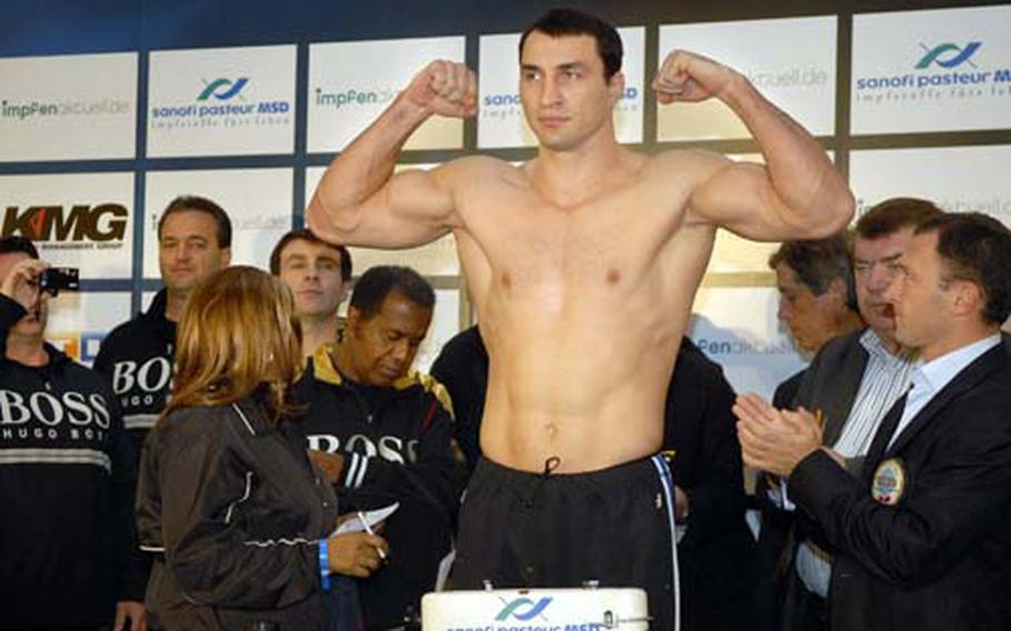 Wladimir Klitschko, the defending heavyweight champion, flexes during his official weigh-in. Klitschko weighed in at 245 pounds, and will face Hasim Rahman Saturday for the title fight.