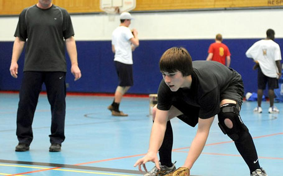 Zack Shull fields a ground ball during practice, as coach Stephen Madl watches in the Ramstein High School gym.