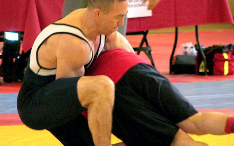 Working from the top in a referee's-position restart, Steve Horton of Ramstein lifts Seth Williams en route to throwing the Bamberg-based wrestler for a five-point move Saturday in a 163-pound bout. Horton won the match by winning the first two of three scheduled rounds.