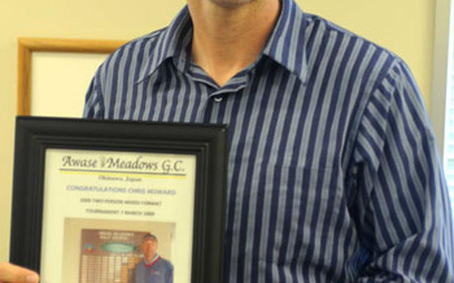 Chris Howard displays a photograph given to him by Awase Meadows Golf Course officials after Howard scored a rare two holes in one during the same golf round on Saturday.