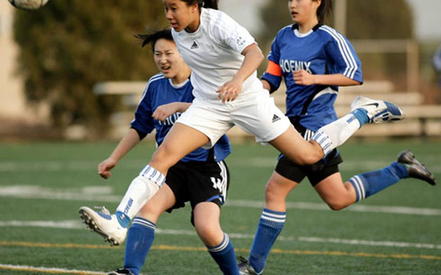 In one of the handful of times she hasn't played goalkeeper, Seoul American sophomore Liz Gleaves heads the ball past Korea International's Michelle Lim, left, and Mina Park during a Korean-American Interscholastic Activities Conference girls soccer match at South Post, Yongsan Garrison, South Korea. The Falcons won 4-0.