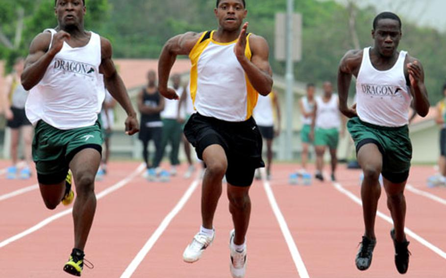 From left, Kubasaki's Marquette Warren, Kadena's Brandon Harris and Kubasaki's Lewis Finney pound for home in the 100-meter dash during Saturday's Okinawa Activities Council track and field meet at Kadena Air Base. Harris won in 11.37 seconds, Warren was second in 11.43 and Finney fourth in 11.71.