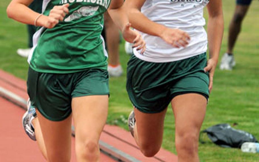 Kubasaki freshman Jessica Powell, left, passes teammate Quirina Cohn near the finish line of the mile during Saturday's meet at Kadena. Powell won in 5 minutes, 54.83 seconds; Cohn was next in 5:55.16.