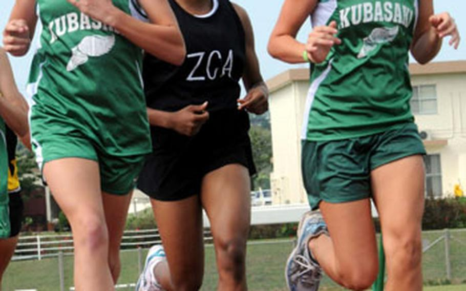 Kubasaki's Abbi Wall, left, and Jessica Powell run at the head of the pack just ahead of Teauna Baker of Zion Christian Academy during Thursday's two-mile run in the third Okinawa Activities Council track and field meet of the season at Camp Foster, Okinawa. Powell suffered her first defeat of the season as Baker, a sophomore and the reigning island champion, stormed past Powell in the home stretch. Baker won in 13 minutes, 0.93 seconds; Powell was second in 13:02.37.