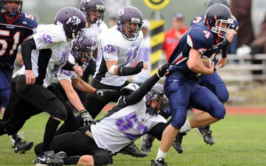 Bitburg senior Derek Waters powers his way for yardage despite the efforts of Mannheim defenders. Bitburg turned back Mannheim 35-0 for its first victory of the season and a successful homecoming Saturday.