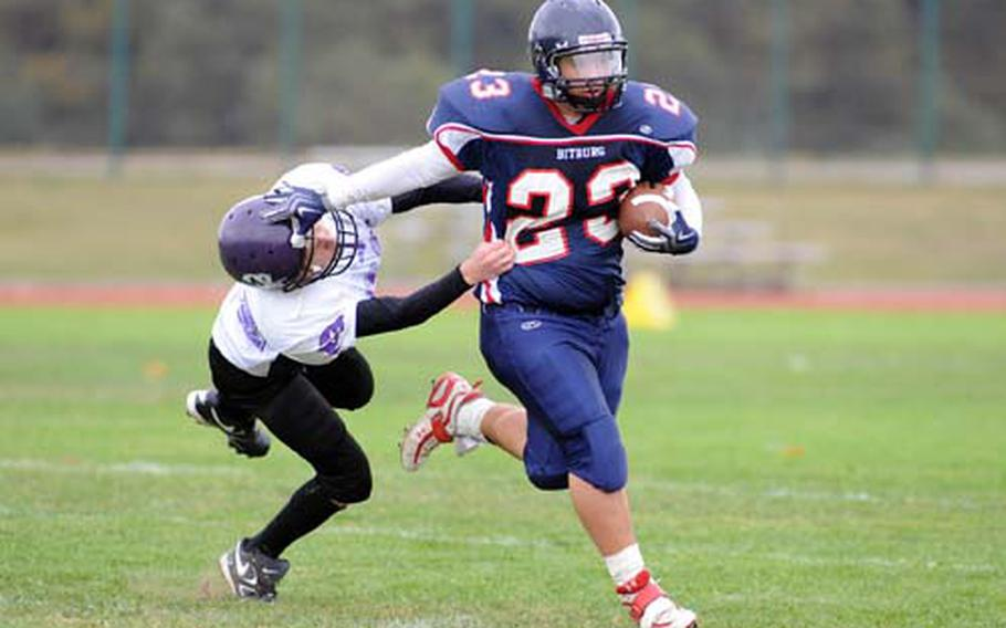 Bitburg's Adam Garcia, right, keeps Mannheim's Justin Sierkowski at arm's length as he rushes for a second-half TD in Bitburg's 35-0 win at home on Saturday.