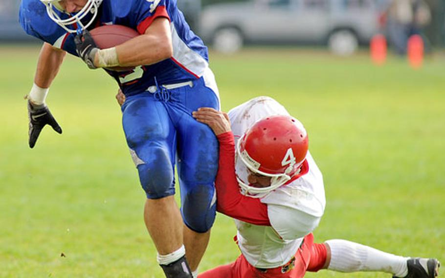 Ramstein's Will Canfield, left, escapes the grasp of Kaiserslautern's Hanawa Hampton on his way to scoring one of his three touchdowns in the Royals 49-0 win over Kaiserslautern on Saturday.