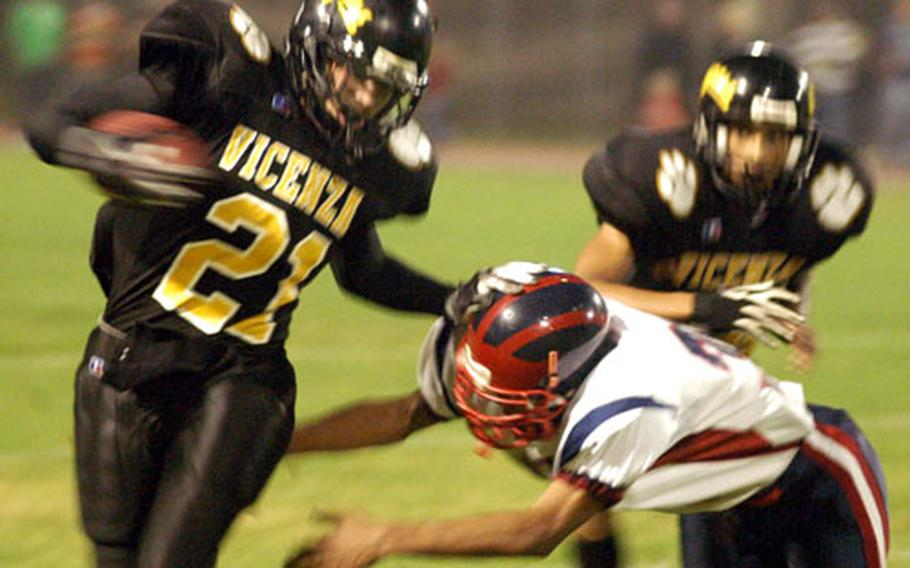 Vicenza's Kyle Kaus stiff-arms an Aviano opponent while rushing for a few of his 90 yards Friday night in the Cougars' 45-7 romp over the Saints.