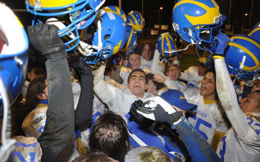 Ansbach Cougars quarterback Dominic Barrale, center, leads his team in celebration following a 48-6 victory over Bamberg on Friday night. It was the Cougars' 29th consecutive triumph, a DODDS record.