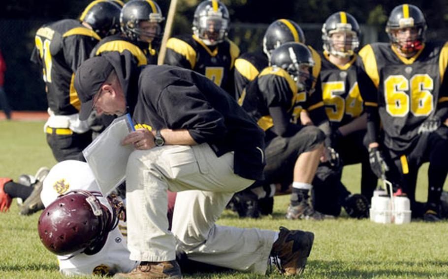 Patch head coach Brian Hill checks on an injured Vilseck player while his team kneels behind him.