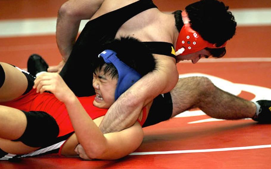 """Harry Bloom of Kadena twists the shoulders of Shonan Military Academy's Yura Naito toward the mat during Saturday's 158-pound gold-medal bout in the 2010 Nile C. Kinnick Invitational """"Beast of the Far East"""" Wrestling Tournament. Bloom pinned Naito in 1 minute, 16 seconds."""