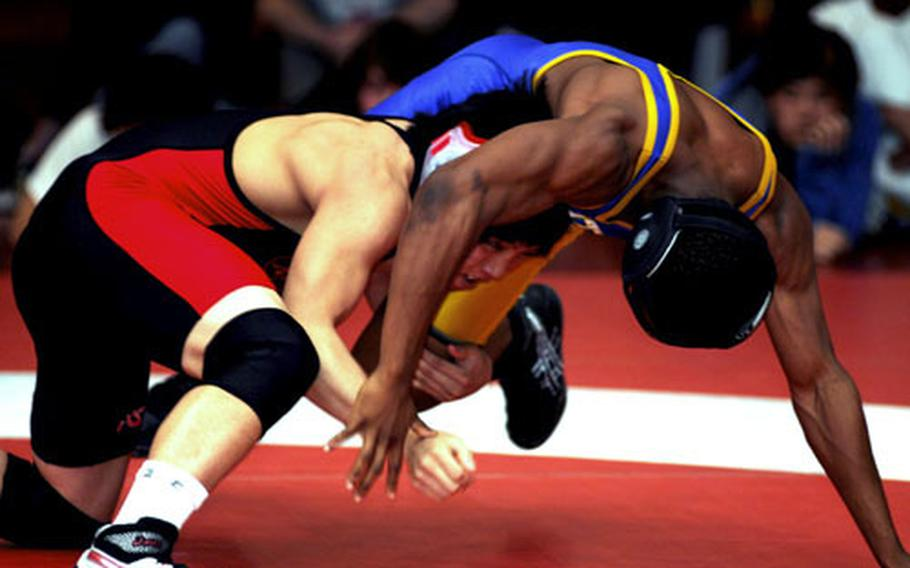 Elijah Gamble of Nile C. Kinnick tries to get the upper hand on Devin Day of Yokota during Saturday's 135-pound gold-medal bout. Gamble decisioned Day 2-0.