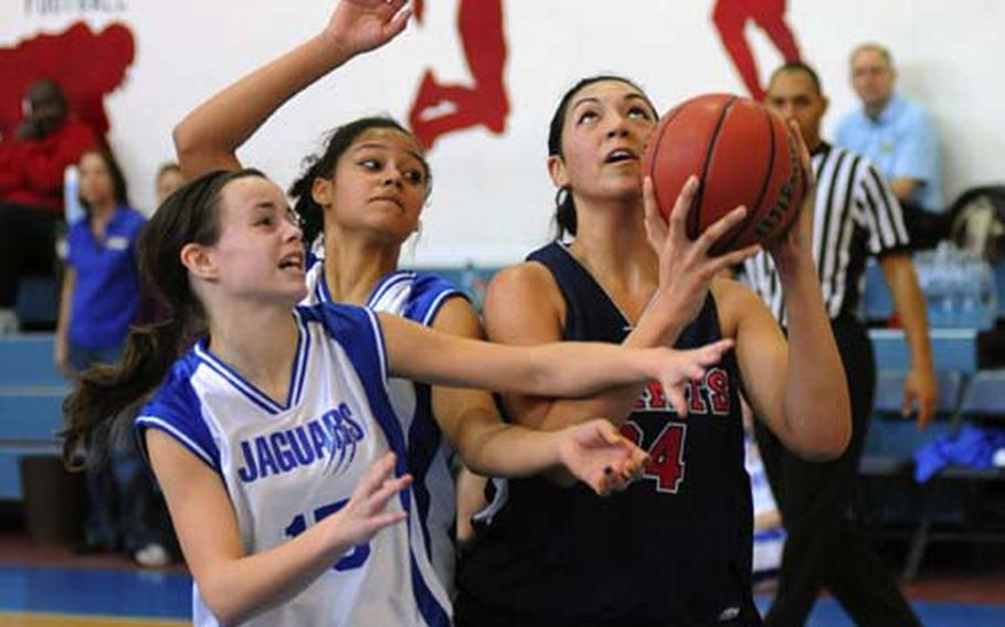 Sigonella's Andrienn Moore, left, and Mekayla Valentine try to keep Aviano's Jasmine Mailoto from getting of a shot in a game in Aviano on Saturday. Aviano won 55-13.