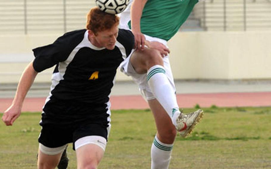 Kadena's Stanley Schrock (4) heads the ball away from a leaping Zach Stallings (12) of Kubasaki during Friday's soccer match at Kadena Air Base, Okinawa. Kadena won 5-1.