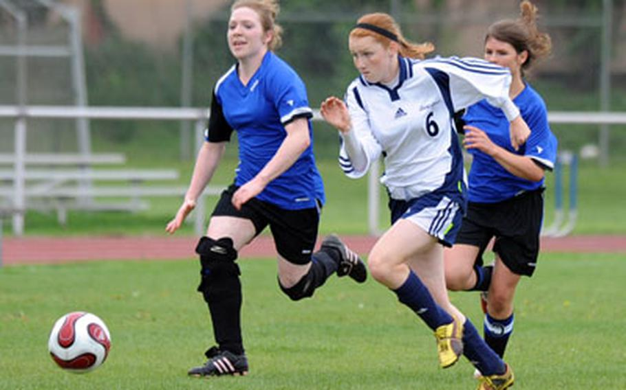 Heidelberg's Steph Miller, center, gets past Emily Adams, left, and Victoria Azera of Hohenfels, on her way to scoring her second of two goals in Heidelberg's 3-0 win at home on Saturday.