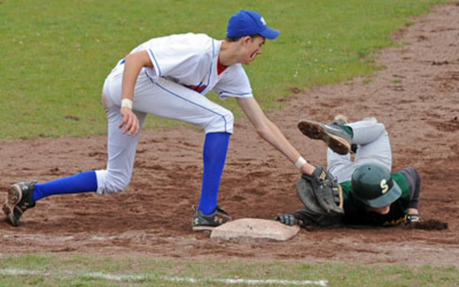 SHAPE's Mitchell Goff, right, gets his hand on the bag before Ramstein's Tyler Breed can put the tag on him in a pick-off attempt at first. Ramstein won the first game of a doubleheader in Ramstein on Saturday, 8-5.