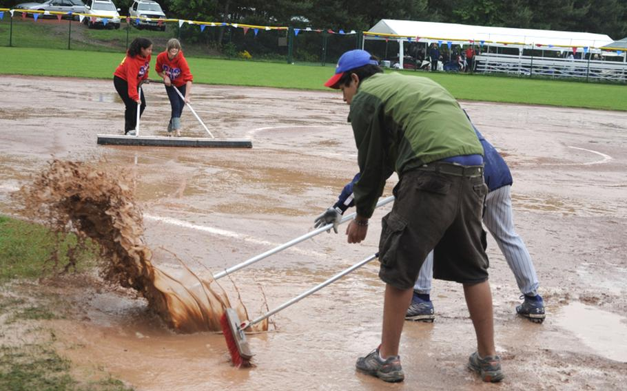 Volunteers work to get water off the field during a rain delay of the high school softball championship tournament on Ramstein Air Base, Germany, on Friday.