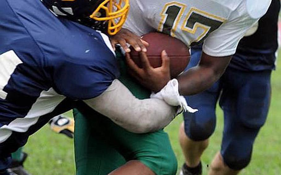 Joint Task Force Wolfpack quarterback Mike Geddie (17) gets dragged down by Yokota Warriors defender Eric Woodcox during Saturday's U.S. Forces Japan-American Football League Torii Bowl championship game at Bonk Field, Yokota High School, Yokota Air Base, Japan. Yokota won 26-23.