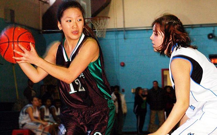 Senior guard Gulee Kwon (12), being defended by Courtney Ouellette of Osan American, is one of six players returning to a Warriors team that will defend the Far East Girls Division II Basketball Tournament title in February on its home floor.