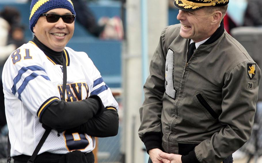 Rear Adm. Peter Gumataotao, left, U.S. Naval Forces Korea commanding officer, and Maj. Gen. John McDonald, U.S. Forces Korea chief of staff, wearing his 1979 West Point jacket, share a laugh before Saturday's Army-Navy flag football game at Sims Field, Seoul American High School,  South Korea. Army prevailed over Navy 12-6 in overtime.