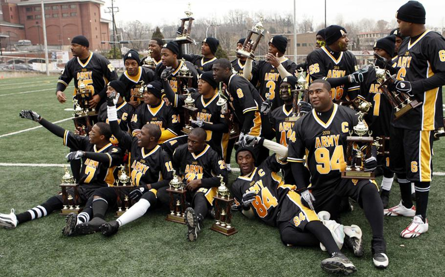 The victorious Army team celebrates with its championship hardware after Saturday's Army-Navy flag football game at Sims Field, Seoul American High School, South Korea. Army prevailed over Navy 12-6 in overtime.