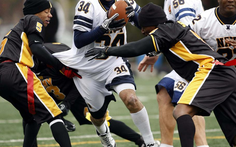 Phillip Lamb of Navy tries to slice between Army defenders Ametrius Shaw and Jamal Smith during Saturday's Army-Navy flag football game at Sims Field, Seoul American High School, South Korea. Army prevailed over Navy 12-6 in overtime.