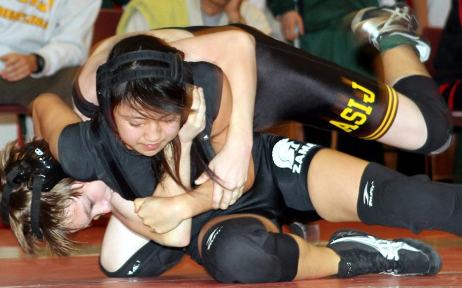 Zama American senior Yurie Tanaka begins to gain a head-in-arm hold on American School In Japan freshman Callan Murphy during Saturday's 108-pound championship bout in the Japan High School Preseason Wrestling Tournament at Nile C. Kinnick High School, Yokosuka Naval Base, Japan. Tanaka pinned Murphy in 1 minute, 35 seconds, becoming just the second girl wrestler to win a gold medal in a Japan tournament, joining Alyssa Rodriguez of Robert D. Edgren four seasons ago.