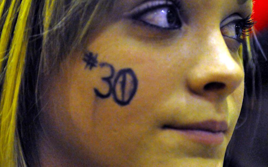 Kadena High School sophomore Rachel Witschen eyes the action, displaying the No. 30 on her right cheek in support of sophomore basketball player Chris Young, during Friday's high school basketball game at Kadena High School, Okinawa. Kadena beat Mirai Tech, 98-62.